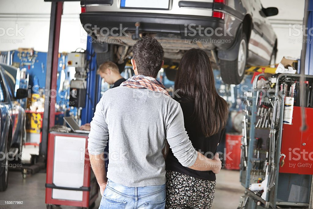 Rear view of young couple in garage royalty-free stock photo