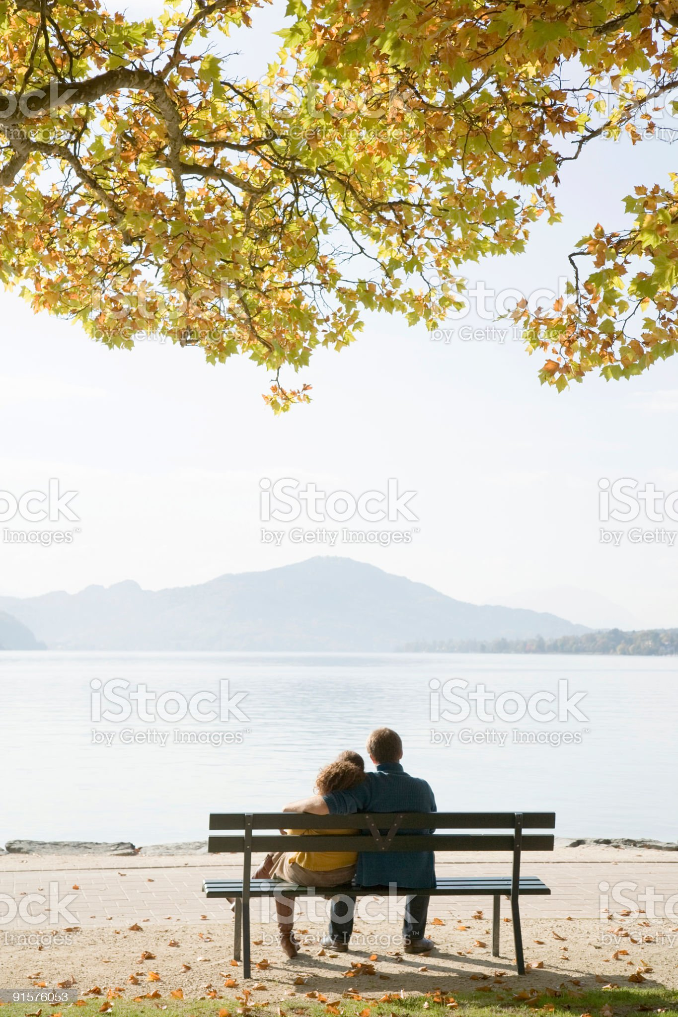 Rear view of young couple sitting embraced on bench lakeside royalty-free stock photo
