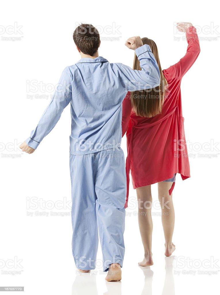 Rear view of young couple sleepwalking stock photo