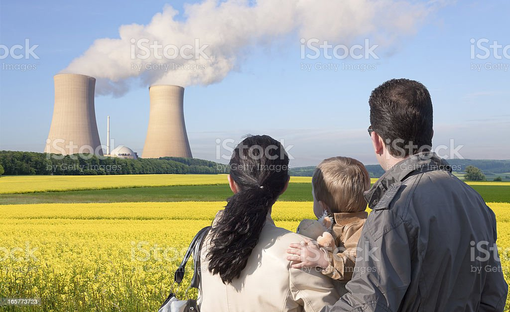 Rear view of young family looking at nuclear power station royalty-free stock photo