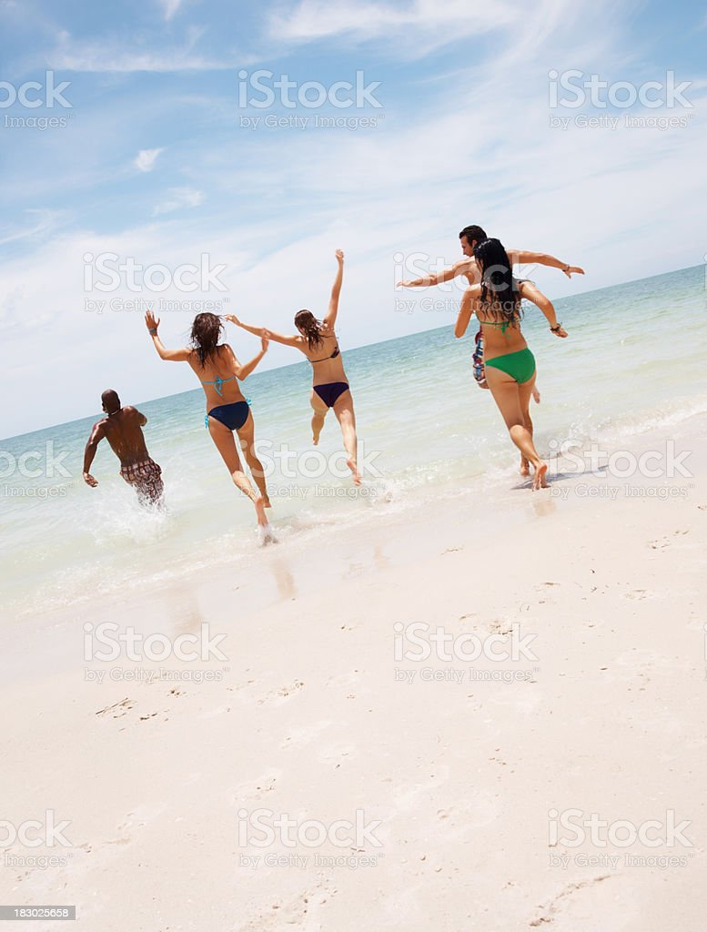 Rear view of young friends running together on beach royalty-free stock photo