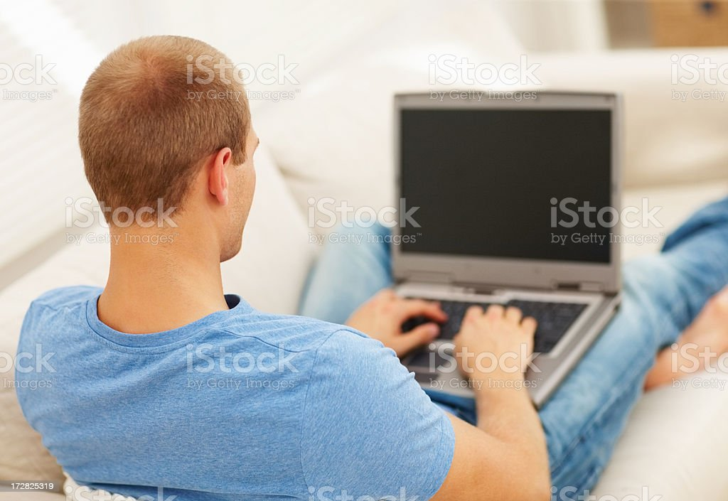 Rear view of young guy using laptop at home stock photo