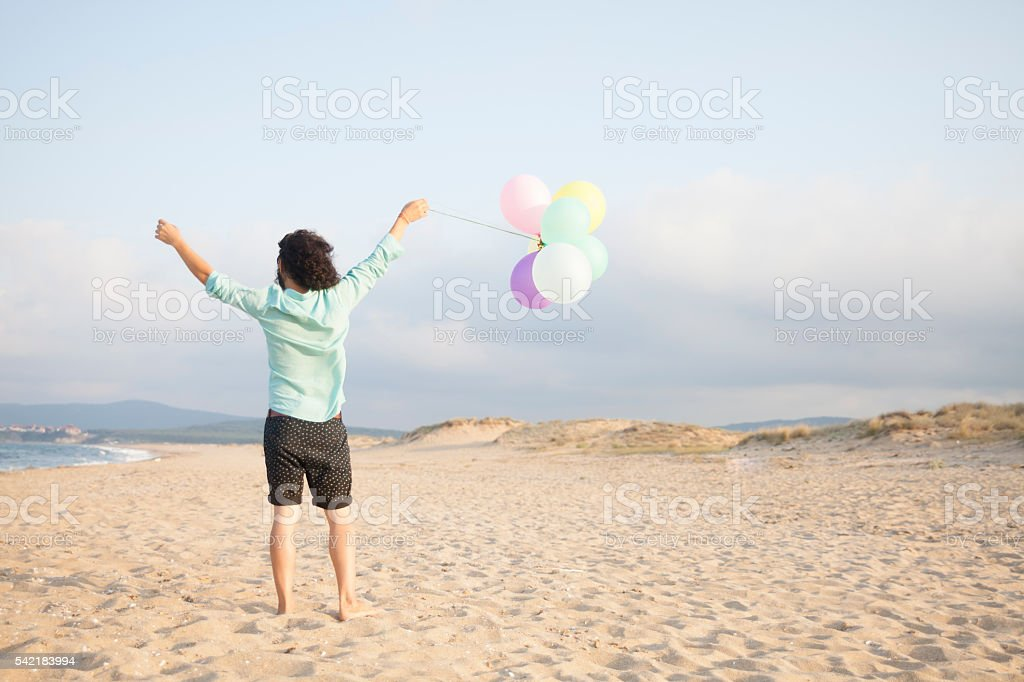 Rear view of young man holding balloons on the beach stock photo
