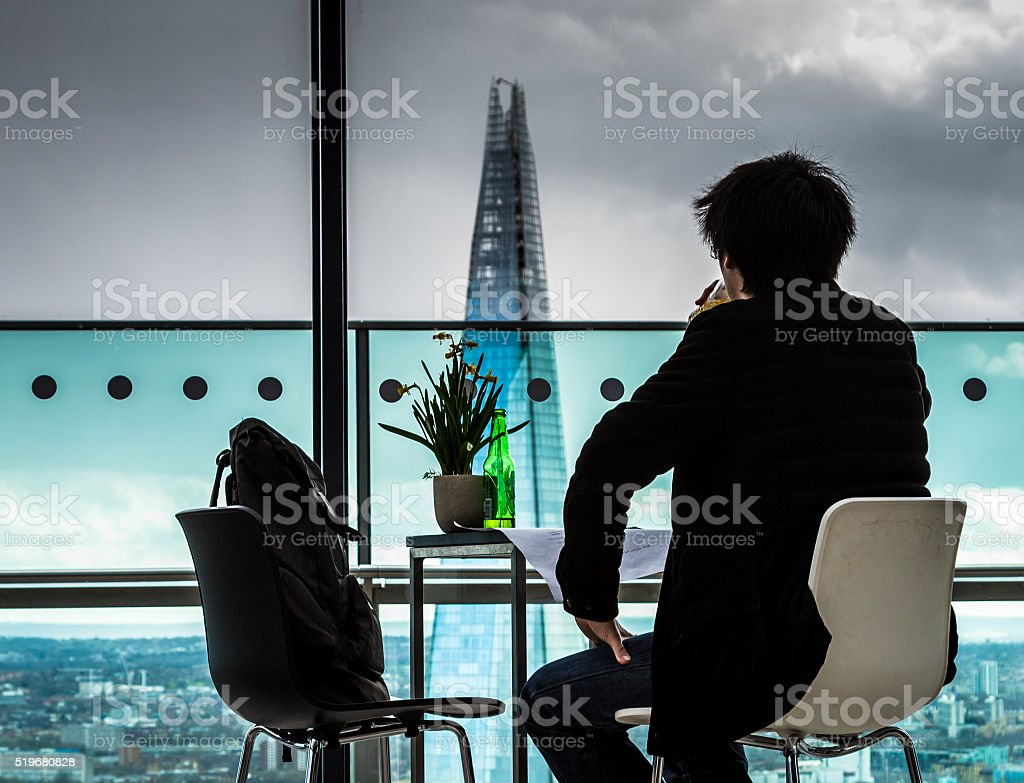 Rear view of Young Man looking out over London Skyline stock photo