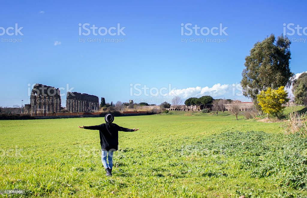 Rear view of young man opening his arms against nature stock photo