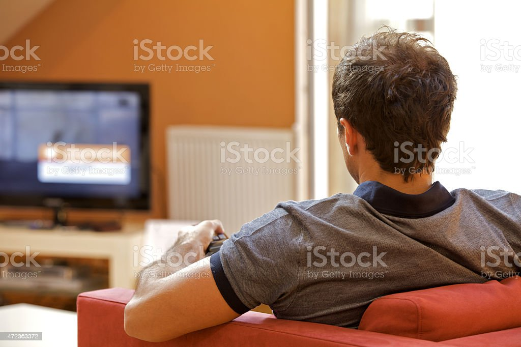 Rear view of young man watching television stock photo