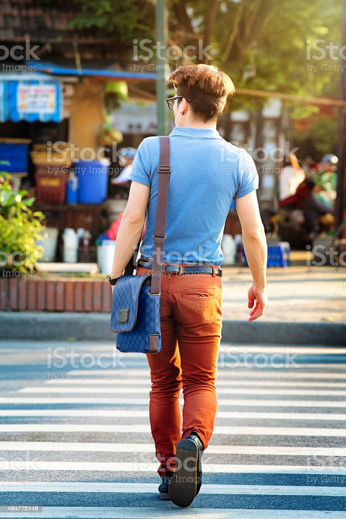 Rear view of young Vietnamese man crossing the street stock photo