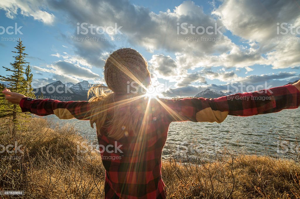 Rear view of young woman arms outstretched by the lake stock photo