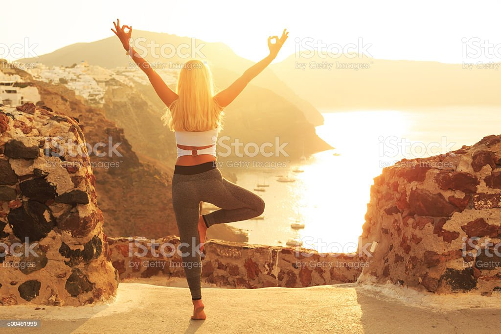 Rear view of young woman at sunset in Santorini Greece stock photo