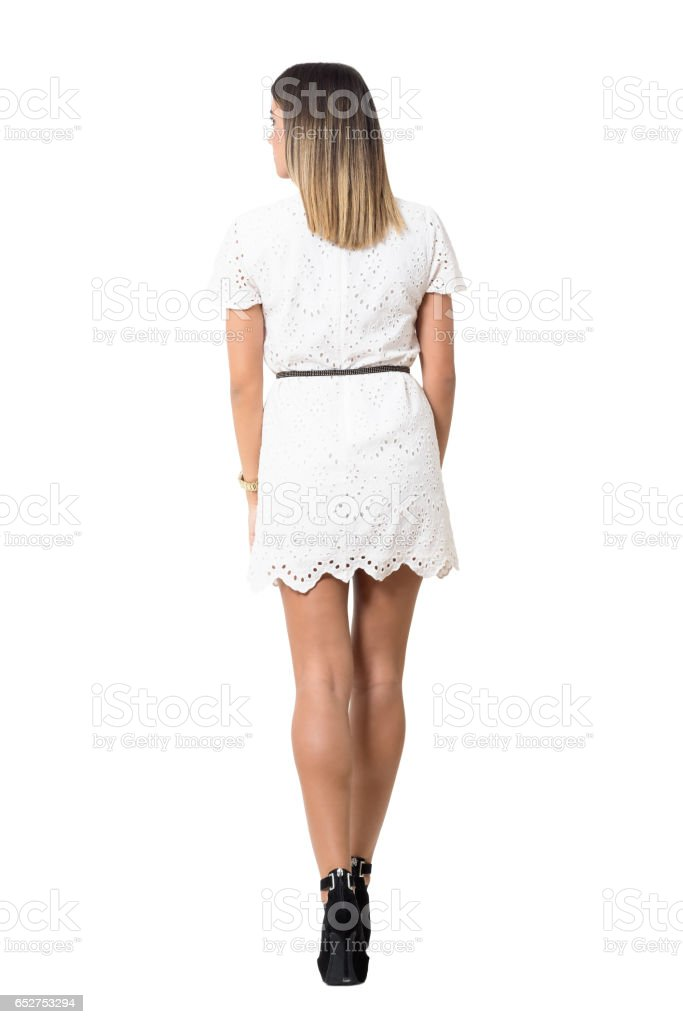 Rear view of young woman in white dress leaving and looking away stock photo