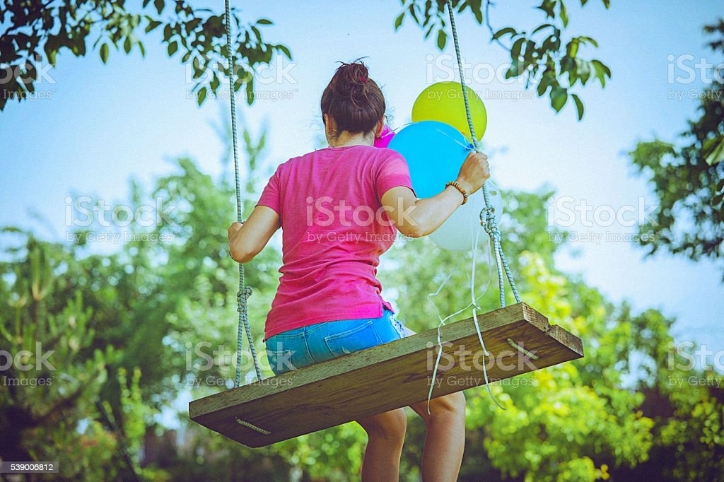 Rear view of young woman on a swing in park stock photo
