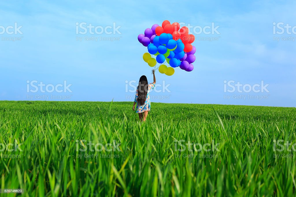 Rear view of young woman with colored balloons stock photo