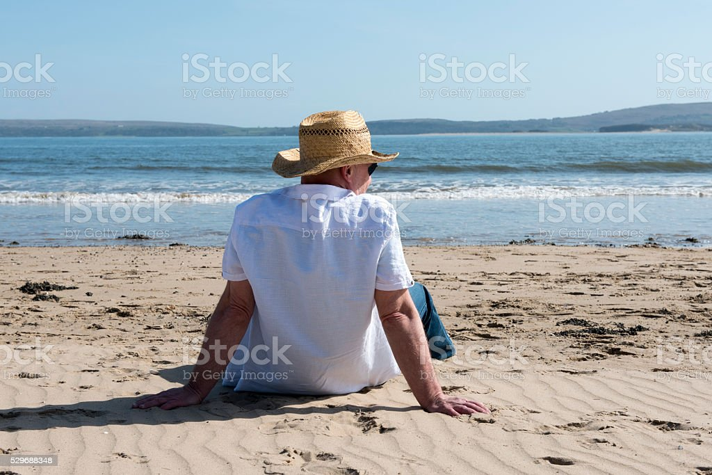 Rear view on a casual mature man on the beach stock photo