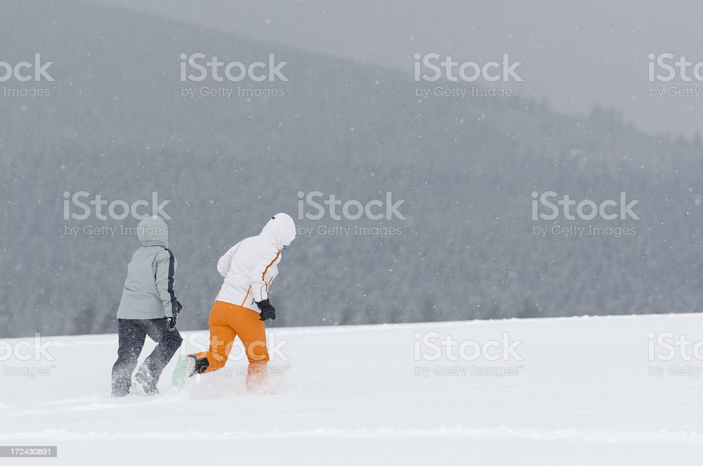 Rear view on two children running over hill in snow royalty-free stock photo