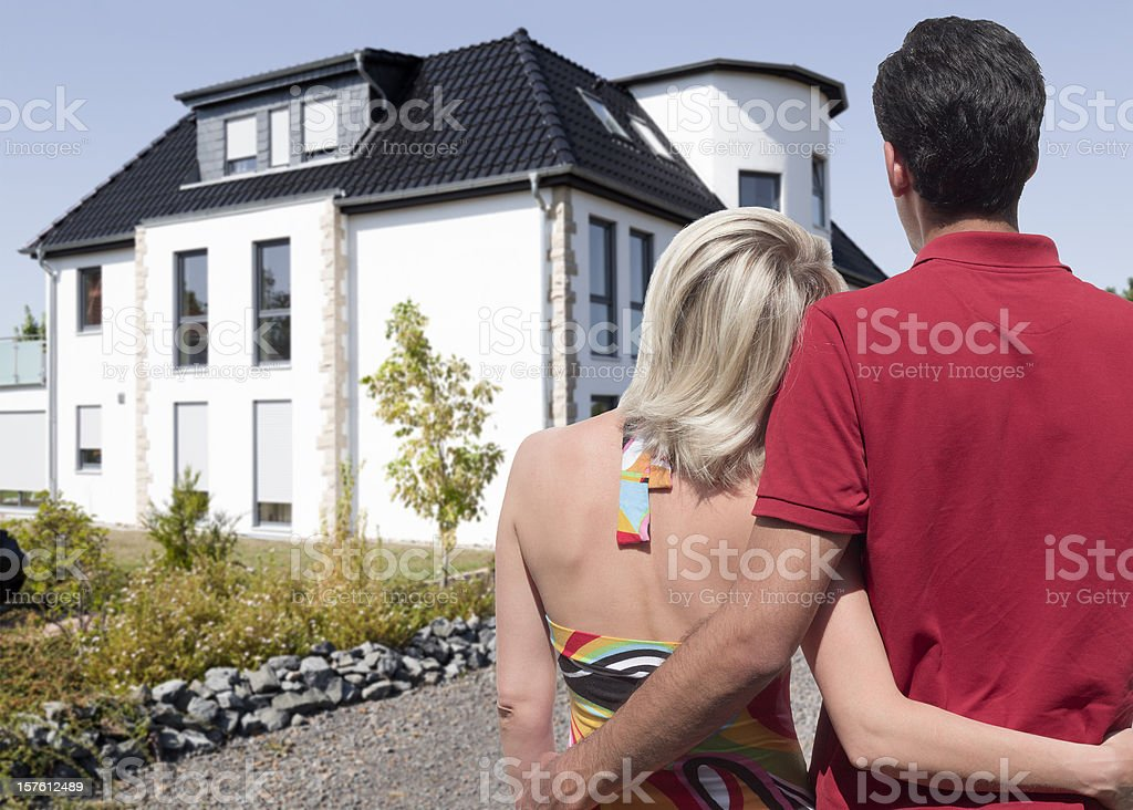 Rear view on young couple looking at beautiful new home royalty-free stock photo