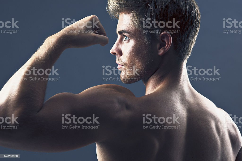 Rear view portrait of man flexing biceps muscles stock photo