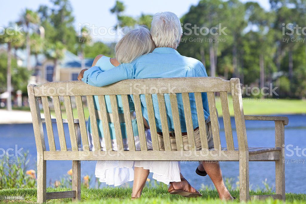Rear View Senior Couple Sitting On Park Bench Embracing stock photo