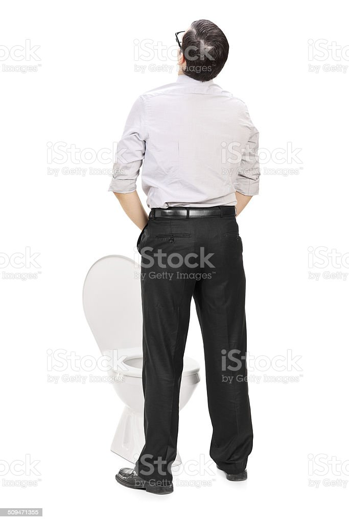 Rear view studio shot of man taking a piss stock photo