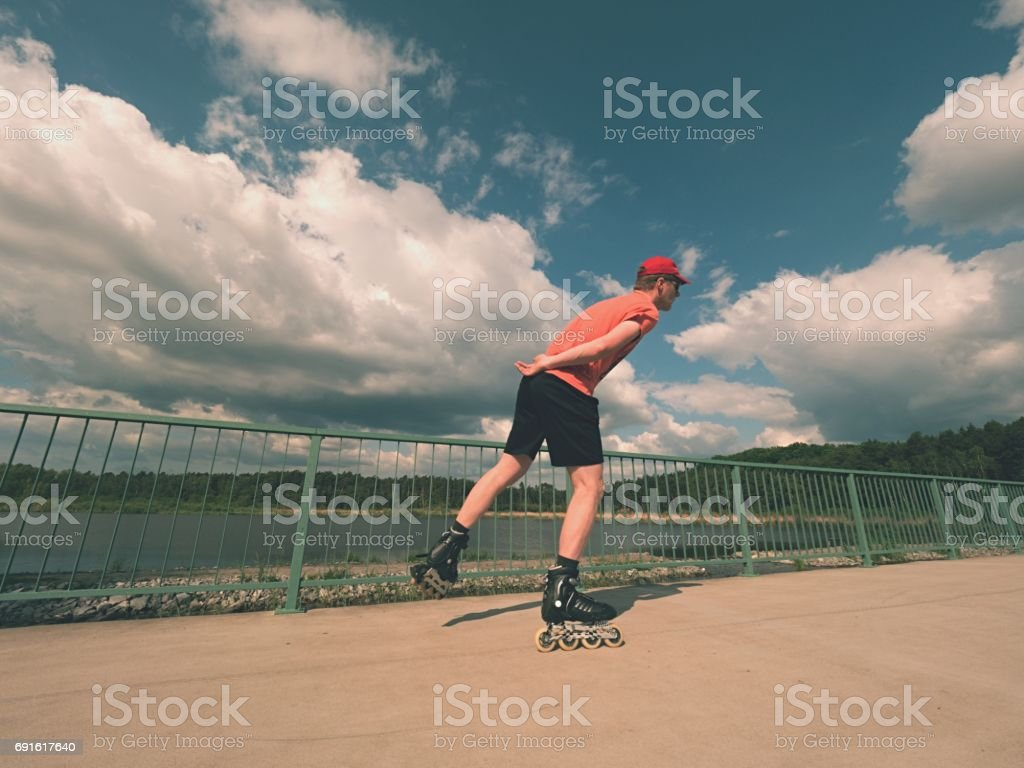 Rear view to inline skater in red t-shirt and black pants skating on the bridge . Outdoor inline skating stock photo
