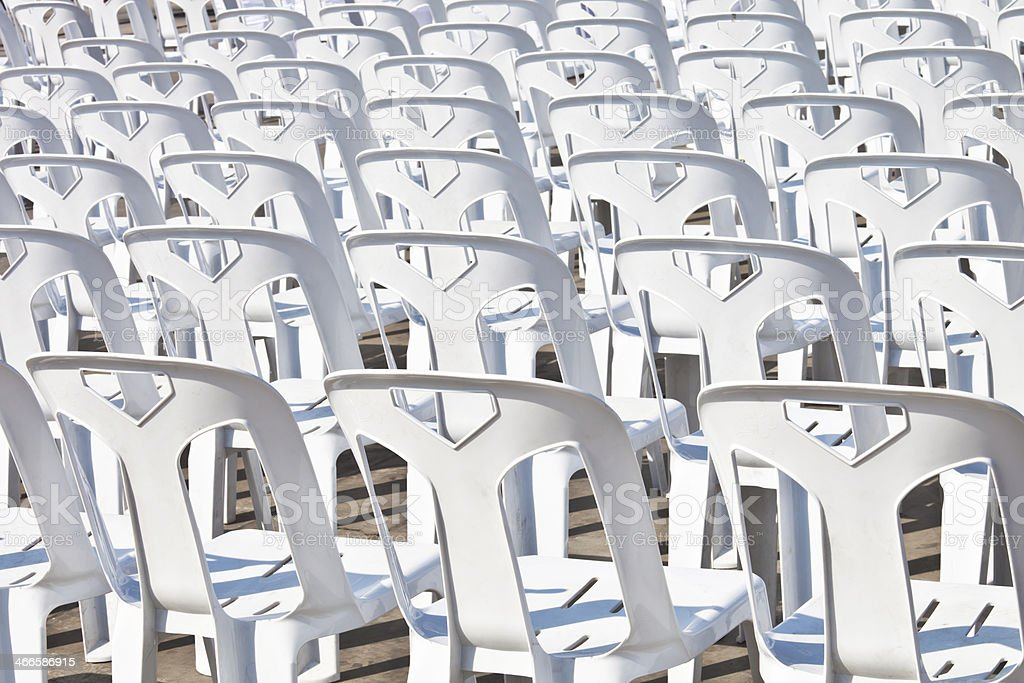 rear view  white plastic chairs  rows outdoor concrete floor stock photo