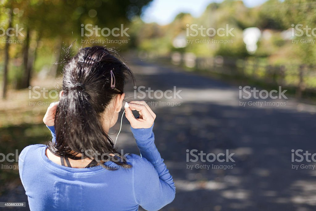 rear view woman with earbuds - horizontal 2 stock photo