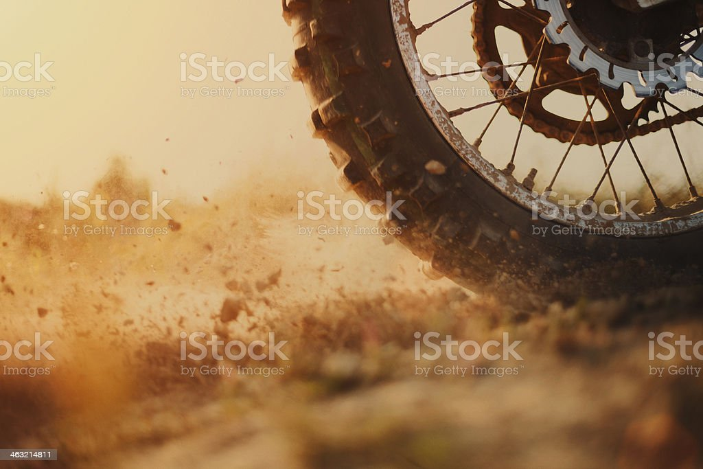 Rear wheel of a motorcross bike kicking up dirt stock photo