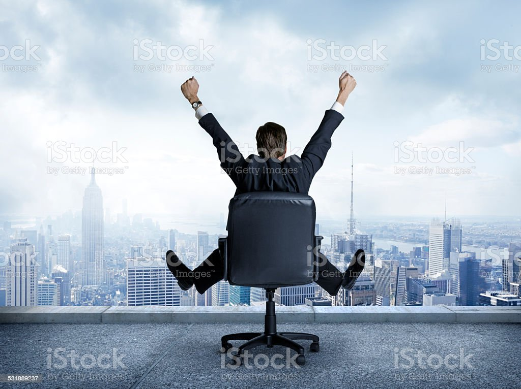Rearview of businessman sitting in chair with outstretched arms. stock photo