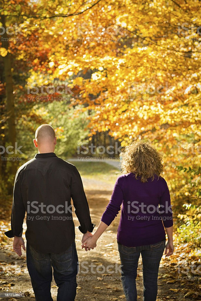 Rearview of Couple Walking Outside in Woods on Fall Day royalty-free stock photo