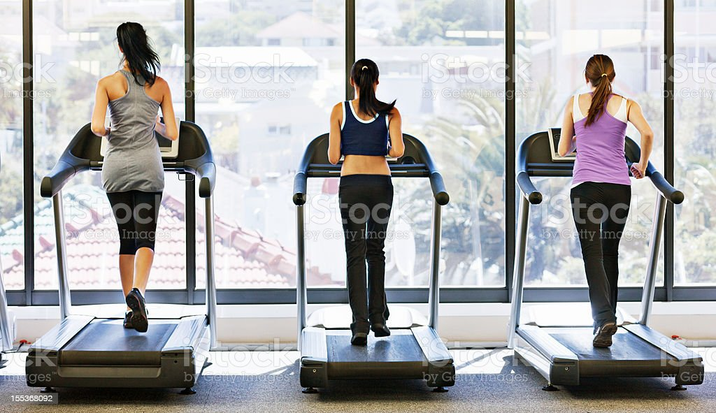 Rearview of three young women runnng on treadmills in gym stock photo