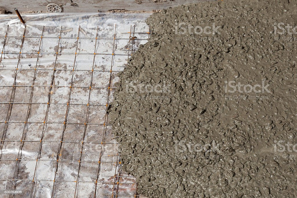 Rebar grids in a concrete floor during a pour stock photo