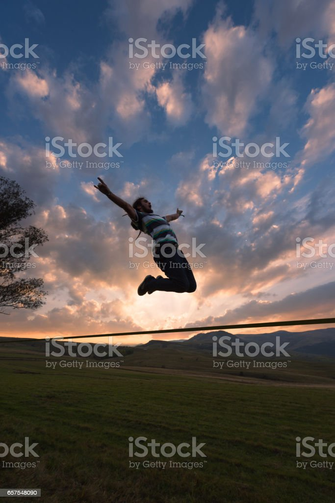 Rebel man jumping on slackline outdoor in nature stock photo