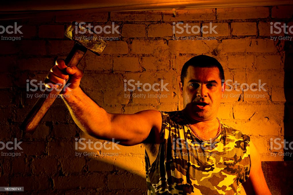 Rebel worker in front of old brick wall with sledgehammer royalty-free stock photo