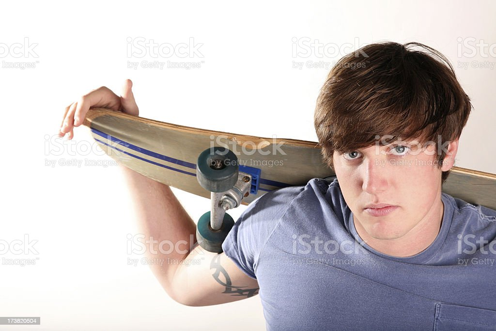 Rebellious Teen with Attitude Tattoo and Skateboard royalty-free stock photo