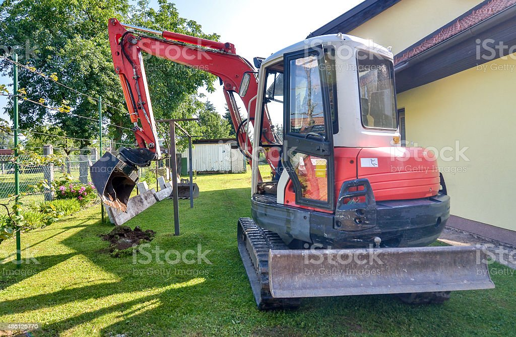 Rebuilding a house and digging dirt with excavator stock photo