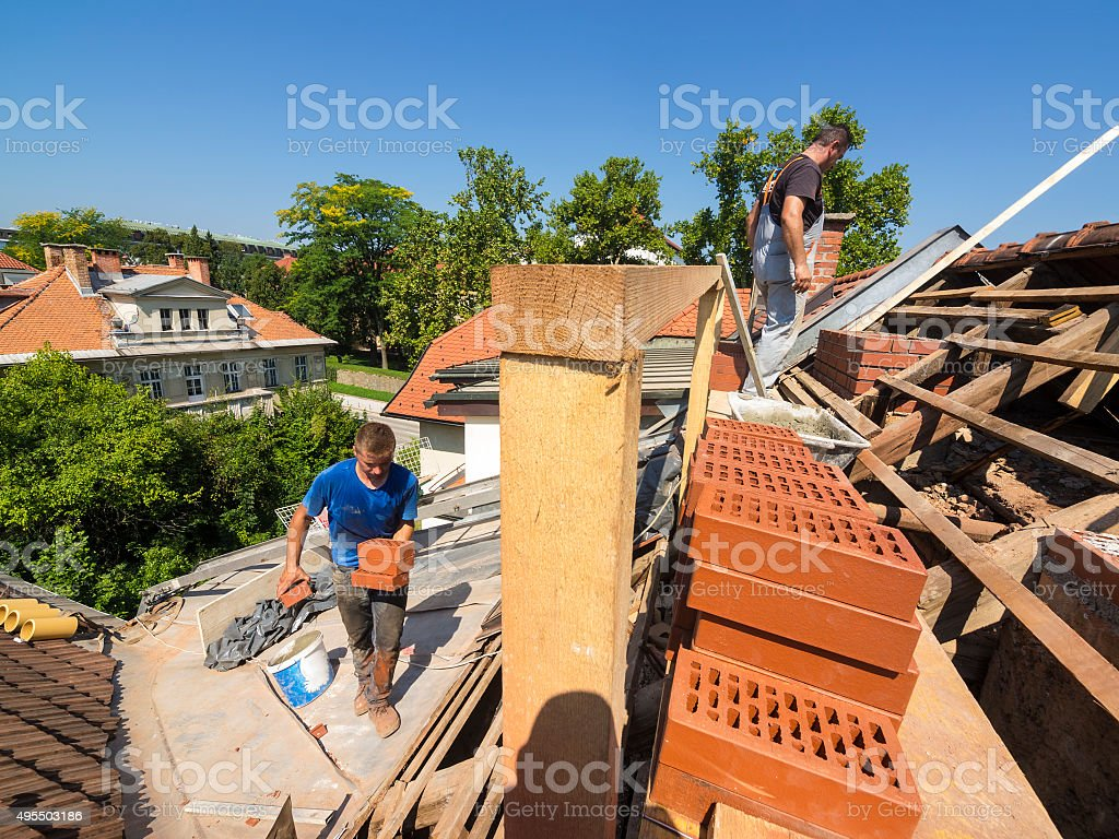 Rebuilding brick chimney on an old roof stock photo