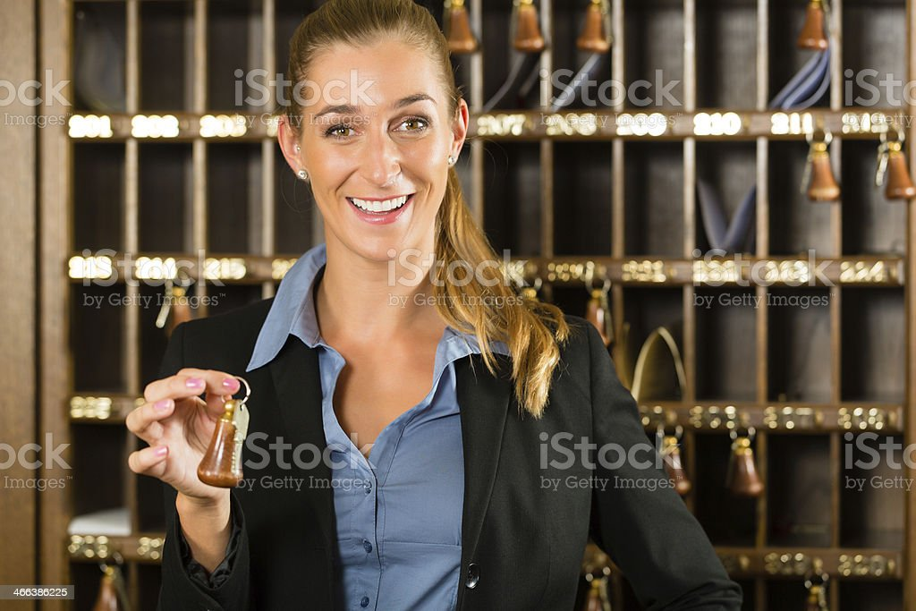 Reception of hotel - woman holding key in hand stock photo