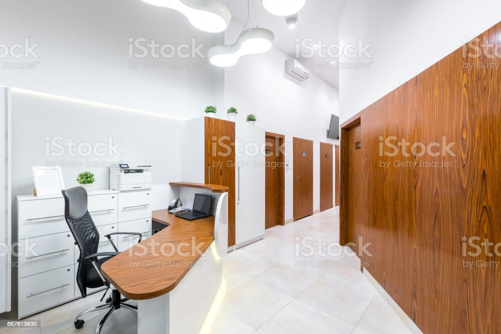 Reception of modern, private clinic with wooden desk, door and wall