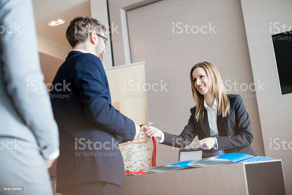 Receptionist giving identity card to businessman at convention center stock photo