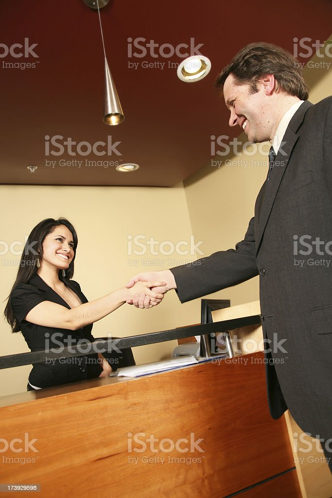 Receptionist Happily Shaking Hands with a Visiting Businessman royalty-free stock photo
