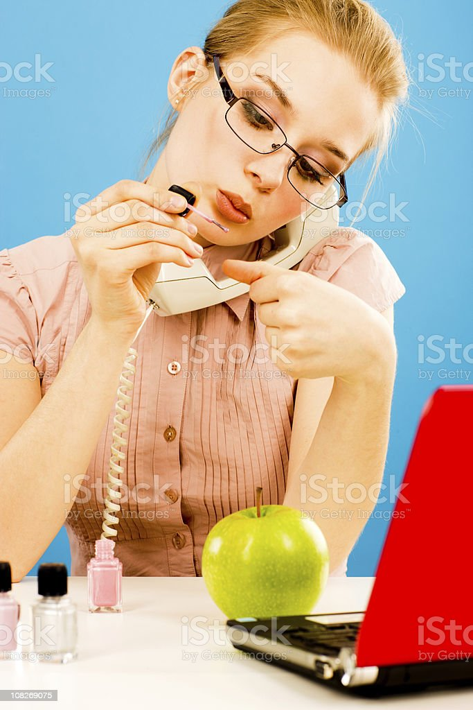 Receptionist Painting Nails While Answering Phone royalty-free stock photo