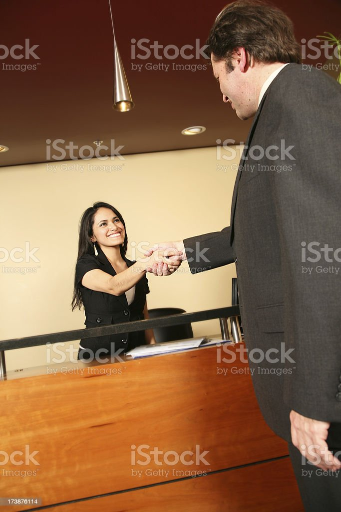 Receptionist Welcoming and Shaking Hands with a Visiting Businessman royalty-free stock photo