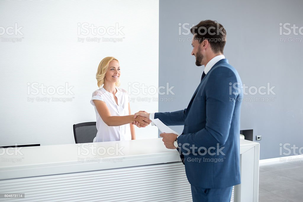 Receptionist wish welcome to guest stock photo
