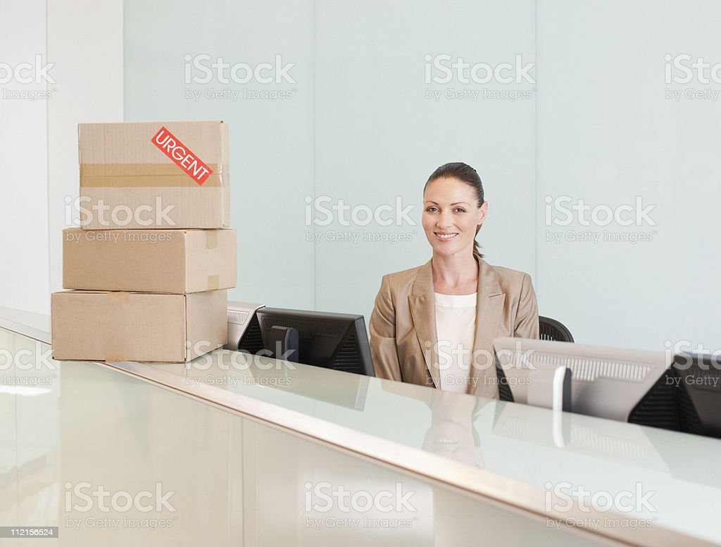 Receptionist with boxes at her desk royalty-free stock photo