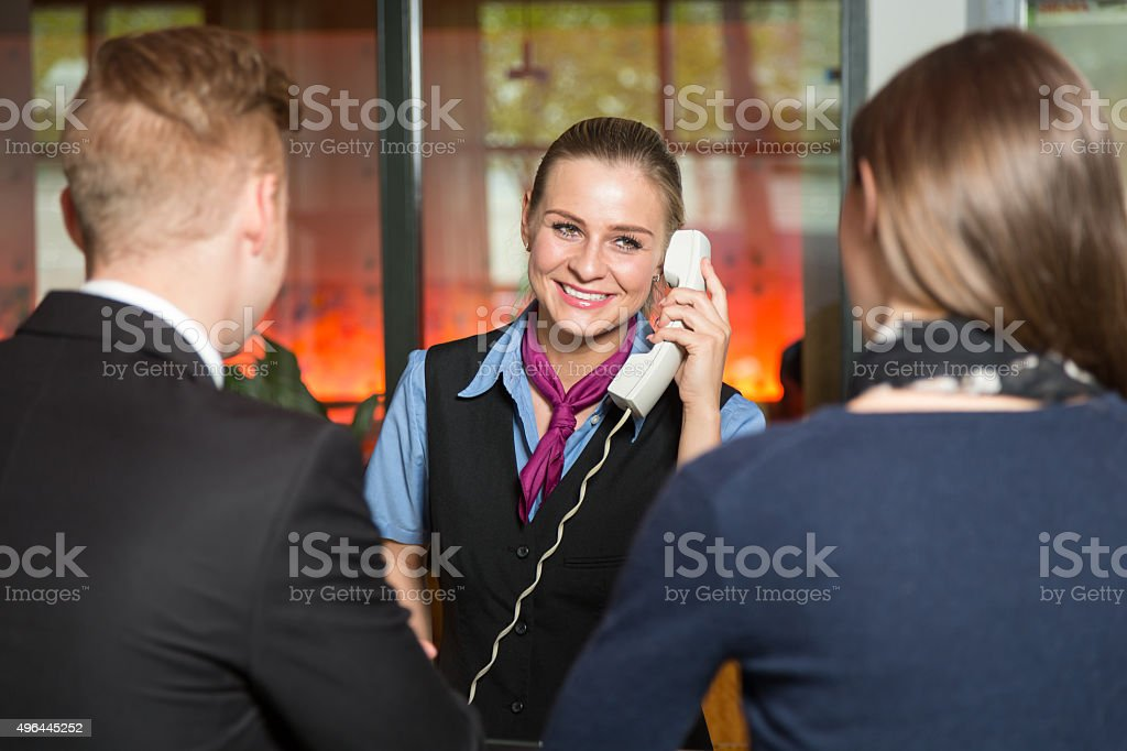 Receptionist with telephone assisting guests in hotel stock photo