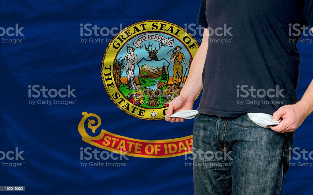 poor man showing empty pockets in front of idaho flag