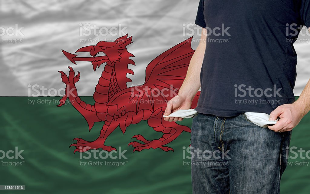 poor man showing empty pockets in front of wales flag