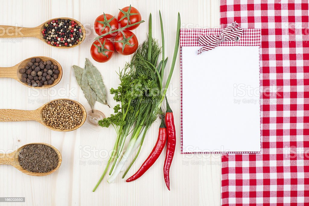 Recipe cook book, chili, cherry tomatoes, spices, tablecloth on wood royalty-free stock photo