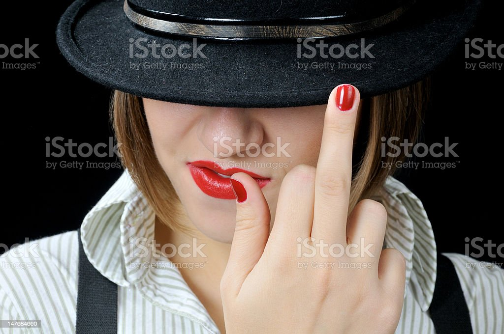 Reckless cool girl in black hat with middle finger up royalty-free stock photo