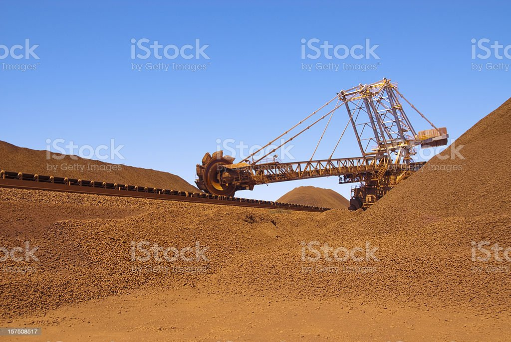 Reclaimer working on an iron ore site under blue sky stock photo