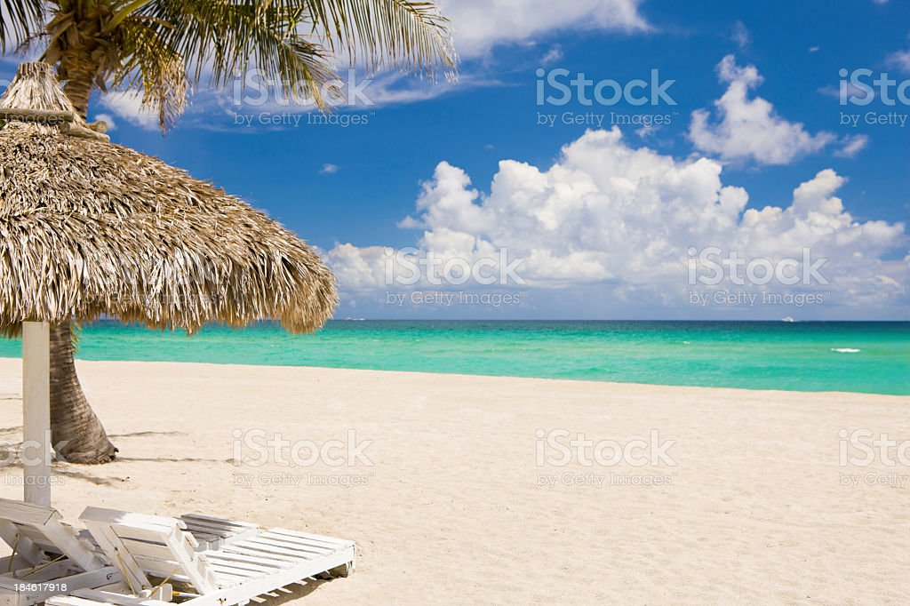 recliners and cabana umbrella overlooking the ocean on a beach royalty-free stock photo